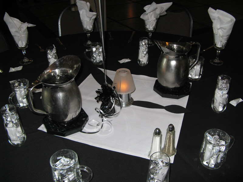 "Table Decor- Black table covers with white napkins.  On the center napkin is a candle lantern, balloon centerpiece and clock hands to carry the ""Moment in Time theme"".  Notice the favors.  The girls had a stemless flute and the boys had mugs.  They were imprinted with the school name, theme and date and filled with white paper covered mints and silver Hershey kisses.<br /> Maneeley's in South Windsor"
