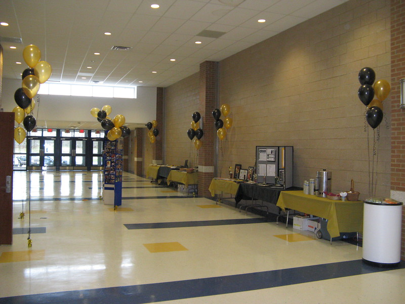 Softball Signing Ceremony- Black and Gold Balloons for Bryant University were used with black and gold table covers.  This large space in the foyer outside the auditorium looked festive filled with balloons.  The picture board in the center was flanked with balloon clouds.<br /> Rockville High School Auditorium