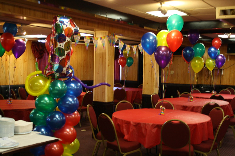 1st Birthday Party- Multi-colored balloons for a family party.  Bunches of 5 balloons on each table with a giant 1 on top of a balloon column.<br /> India Kitchen in Manchester