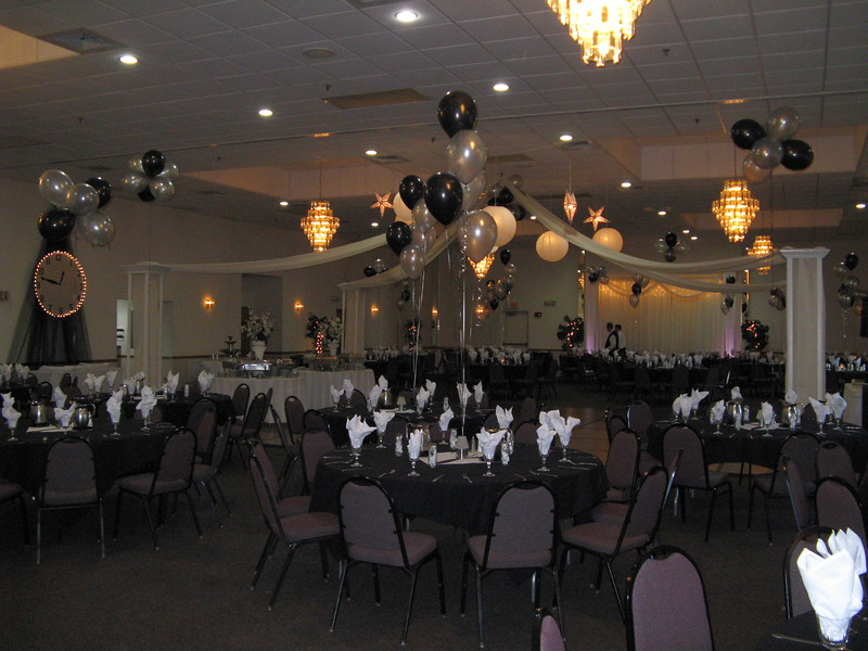 "Silver and Black Prom-  The theme was ""A Moment in Time"".  We did a balloon arch to greet guests in the foyer, dance canopy with balloon center and lighted white and silver round and star lanterns, a giant clock behind the ice sculpture, and balloon centerpieces with clock hands in the center of the tables to carry the theme.<br /> Maneeley's in South Windsor"