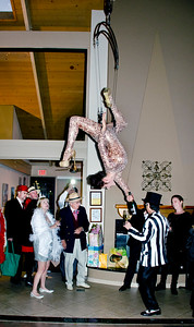 Female acrobat suspended from rope and pouring wine - Sheila Ash birthday party
