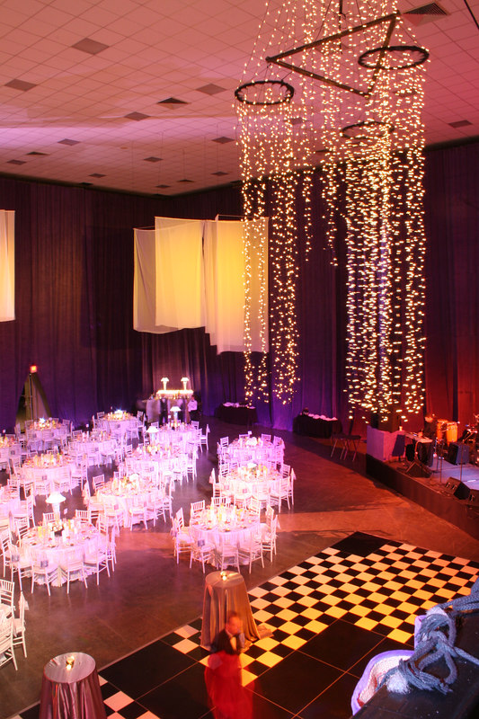 Using purple celvet wall coverings and white linens and chairs created an exciting environment for this Gala.
