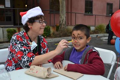 DSC_ Trudy Egan paints a reindeer on Emiliano Cabella's face 1447