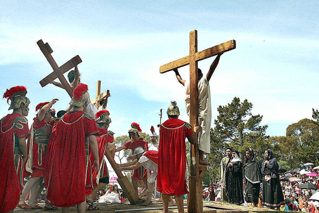 . Actor portraying Jesus in the Passion Play is raised on the cross on hill in Watsonville\'s Ramsay Park on Friday. (Dan Coyro -- Santa Cruz Sentinel)