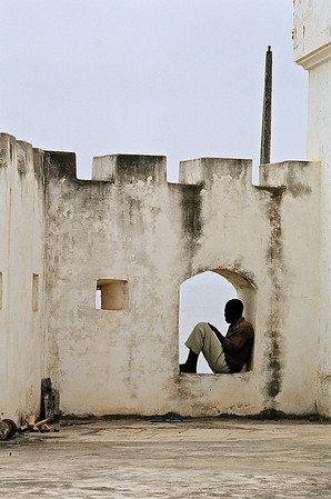 A man sitting in the window of the Cape Coast Castle Museum in Ghana