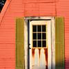 Green shutters frame the white door of the orange framed building.