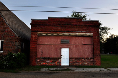 White door, red brick building, boarded up on Main Street, Shaw MS