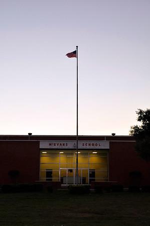 Flag over McEvans High School, lights on at dusk.