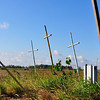 Three crosses, a poll and an electrical line in a field.