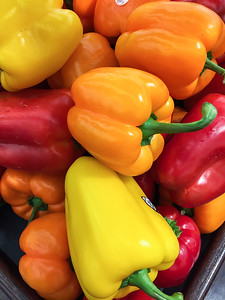 2016-12-06 – I was just walking through the Smiths grocery store and spotted these multicolored peppers. They were so colorful I had to stop and take a photo. I especially liked the green stems against the bold colors.