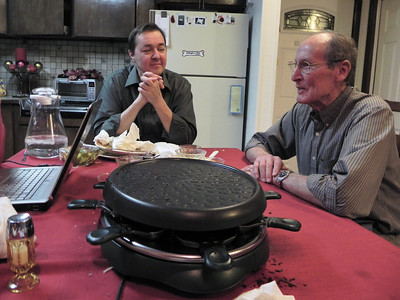 2011/12/27 – We had a nice dinner at my parents home this evening. We had raclette. You cook on the raclette grill shown in the foreground. The entire meal you are cooking what you eat. It is a very social dinner. My cousin, Troy, and his family joined us. They were visiting from Sacramento, CA. Troy is at top center and my dad is on the right. We were done eating and just sitting around shooting the bull.