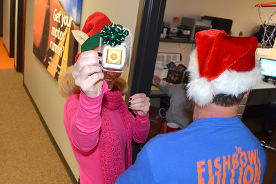 2011/12/15 – Santa and his little elf visited all the employees at Fishbowl today. They handed out early Christmas gifts to every employee. They gave everyone a 2GB Apple Shuffle. Ironically one of our partners sent nice headphones for every employee. There was no collaboration between the two so it was a surprise that they happened on the same day. The elf is our president (Mary) and Santa in the blue shirt on the right is our CEO (Dave).