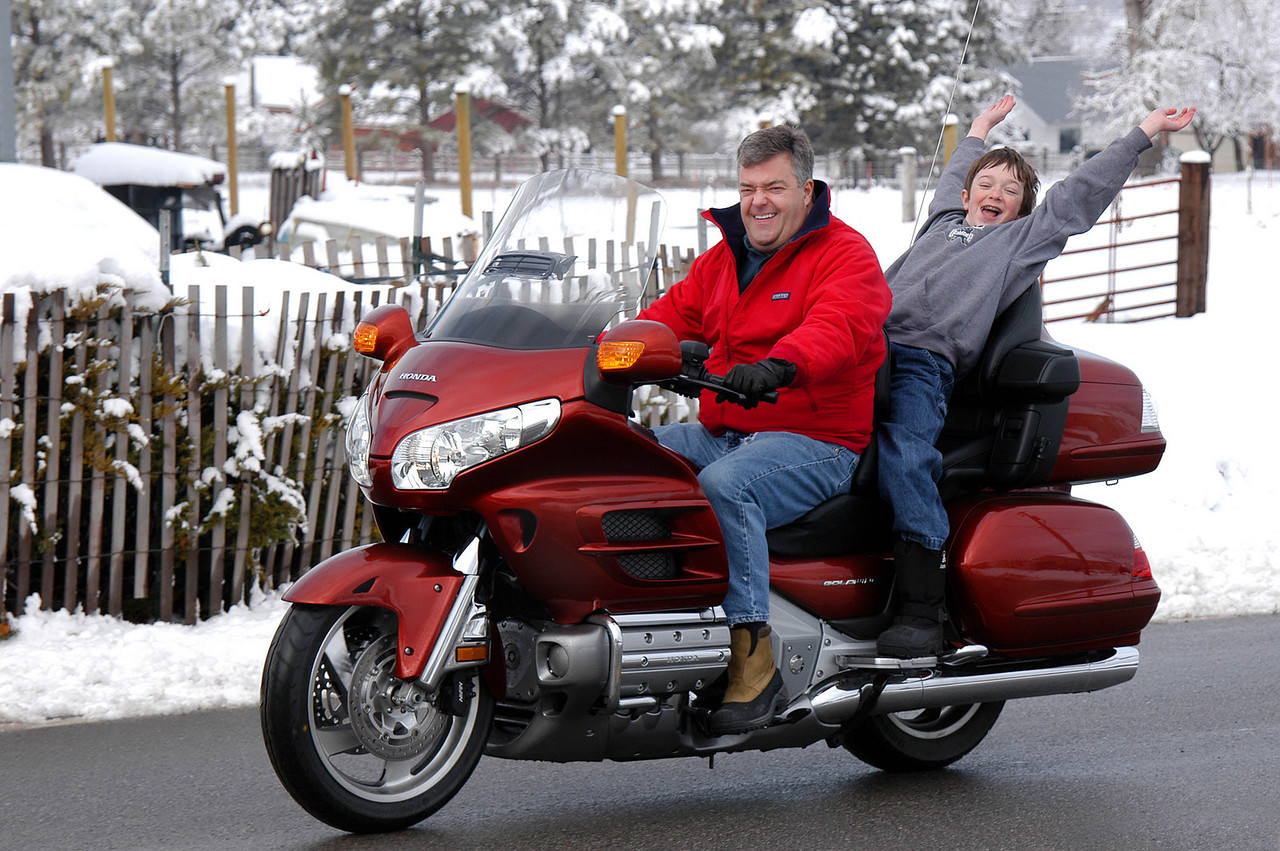 2/19/07 – Steve turns 50 in March and has been planning the purchase of his birthday gift for a very long time. He just got it this week – a Honda Goldwing. Unfortunately it snowed heavily overnight making anything more than a short ride little fun. Of Course Scott seems to be having a great time riding behind his dad.