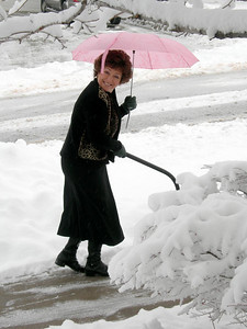 12/9/07 – I had to quickly grab a camera to get this picture of Lisa. She was all dressed up and ready for church but couldn't resist picking up a shovel to clear a little more snow from the driveway and sidewalks. I had to laugh at her because of the pink umbrella in one hand and the shovel in the other that made it awkward to control either.