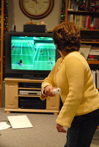12/29/07 – We've had so much fun playing Wii I went out and bought one, but it wasn't easy. They've been sold out for weeks in the stores and the online sellers wanted hundreds of dollars more than retail. I found one online that was very under priced and the seller happen to be about 2 miles from our home so I rushed over and paid cash for it before he could get a better offer. I only paid $22 more than retail, so I felt very good about the deal. This is Lisa playing Tennis with Jessica. You can get an excellent work out just playing these games.
