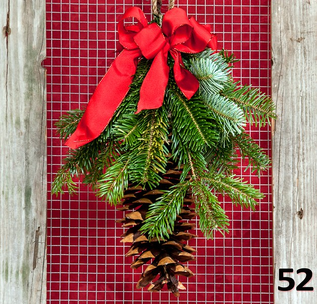 #52 - Large sugar pine cone with a simple decor of fresh PNW greens, bow and sisal hanger.
