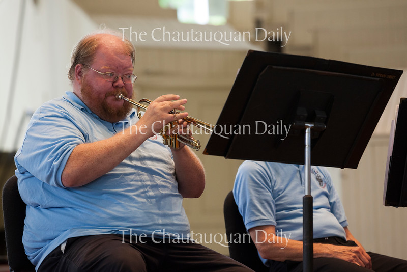 Soprano cornettist Nate Barnes demonstrates his instrument on the prompting of conductor William Cocoa at the Buffalo Silver Band's 2:30 PM performance on July 3, 2016, in the Amphitheater. <br /> <br /> Instead of having an intermission during the performance, Cocoa led a segment in which individual members of the group demonstrated their respective instruments to educate the audience about lesser-known brass instruments like the flugelhorn and the euphonium. <br /> <br /> Photo by Carolyn Brown.