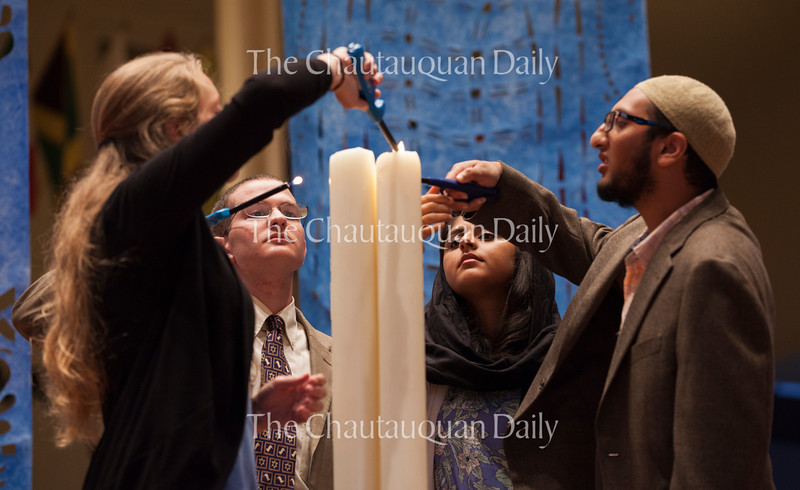 "From left: Abrahamic Program for Young Adults Christian Coordinator Emily Peterson, Jewish Coordinator David Bloom, Muslim Coordinator Safia Lakhani, and Muslim Coordinator Yasin Ahmed light three candles representing the three Abrahamic faiths, Christianity, Judaism, and Islam, <br /> at the Sacred Song Service, ""The Family of Abraham Seeks Courage to Change,"" at 8 PM on July 31, 2016, in the Amphitheater. The APYA coordinators led the service and delivered speeches about interfaith understanding and tolerance. Photo by Carolyn Brown."