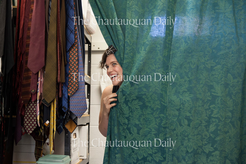 "Actress Kathryn Metzger, who plays Catherine Givings in the Chautauqua Theater Company's production of ""In the Next Room (or the vibrator play),"" peeks out of the changing room in the costume shop of Brawdy Theater Studios before her quick change rehearsal on June 27, 2016. During the rehearsal, Metzger had to make sure that she could change out of her character's dresses as quickly as the scene changes in the play require -- in one case, in 40 seconds or faster. Photo by Carolyn Brown."