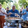 Bluie Greenberg, center, and Richard Parlato, right, serve themselves food at the Volunteer Recognition Party at 5:30 P.M. on Tuesday, July 26, 2016, on the Athenaeum Hotel Porch. The event included a special presentation by the day's morning lecturer, Nalini Nadkarni. Photo by Carolyn Brown.