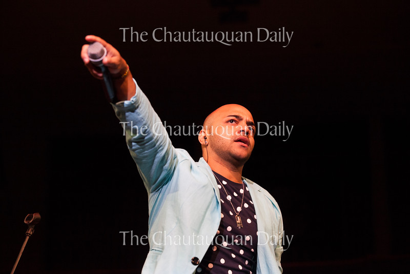 Tiempo Libre lead vocalist Xavier Mili holds his microphone out to the audience during a call-and-response song in the Amphitheater on June 28, 2016. Tiempo Libre's Cuban songs inspired many audience members to sing and dance along. During the show, Mili invited a lively crowd of dancing Chautauquans to join him and the band onstage. Photo by Carolyn Brown.