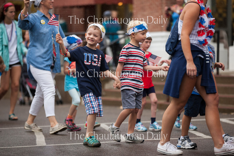 Arik Oskvig, left, five, waves an American flag to the crowd while walking toward the steps of the Colonnade on with Mason Arnold, right, five, on July 1, 2016.<br /> <br /> Oskvig and Arnold joined the other children and teachers of the Children's School to sing patriotic songs on the Colonnade steps and show off the patriotic apparel that they had made earlier that week. <br /> <br /> The parade was held on the Friday before the Fourth of July because the holiday officially falls on a Monday, which would give newcomers to Children's School no time to prepare for the parade. The parade was almost relocated due to rain, but the skies cleared up enough for the children to march to the Colonnade along their traditional parade route. <br /> <br /> Photo by Carolyn Brown.