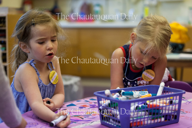 Jillian Sears, left, four, and Aubrey Olson, right, four, color with markers in the Purple Room at 10:45 AM on July 1, 2016, at Children's School. Children at Children's School enjoyed a variety of activities, including coloring, face painting, and playing with toy cars, before the annual Independence Day Parade that morning. Photo by Carolyn Brown.