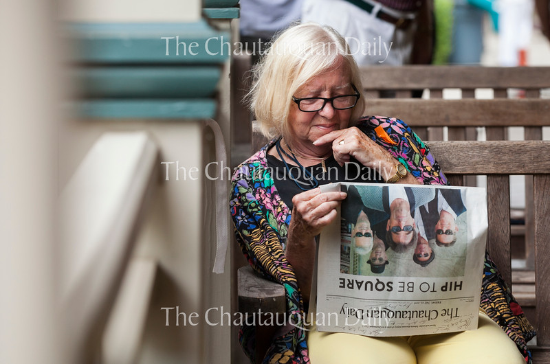 "LaDonna Bates reads a copy of the Daily before a Chautauqua Institution Trustees Porch Discussion entitled ""Family & Youth Experiences and Programs"" at 12:30 PM on July 22, 2016, on the porch of Hultquist Center. At the event, Sherra Babcock, vice president and Emily and Richard Smucker Chair for Education, and Matt Ewalt, associate director of education and youth services, talked about the work that they do to enhance young Chautauquans' summer experiences with community programming and other outreach efforts. Photo by Carolyn Brown."