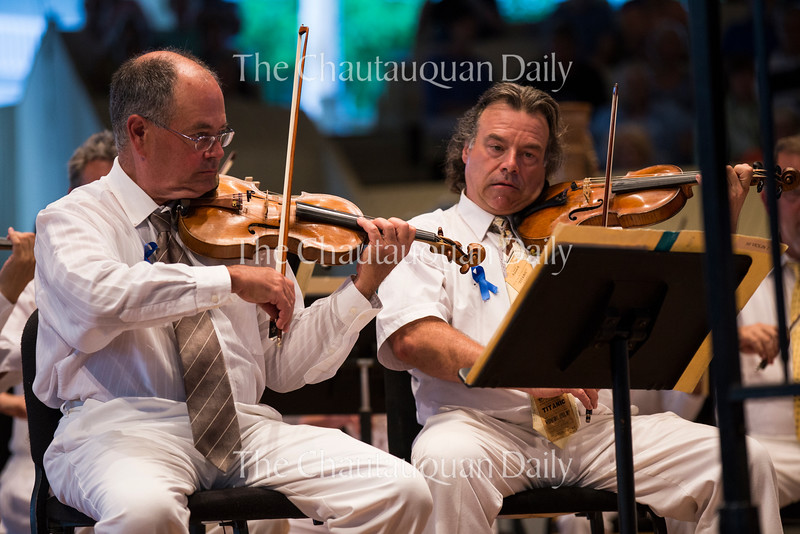 Brian Reagin, left, and Vahn Armstrong, right, play the violin in the Chautauqua Symphony Orchestra's concert at 8:15 PM on July 14, 2016, in the Amphitheater. Teddy Abrams of the Louisville Orchestra was the guest conductor. Photo by Carolyn Brown.