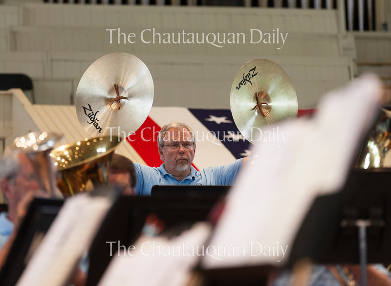 "Steve Bell strikes the cymbals together during the Buffalo Silver Band's rendition of the national anthem at the beginning of their 2:30 PM performance on July 3, 2016, in the Amphitheater. <br /> <br /> Although the Buffalo Silver Band plays in the style of British brass bands, the theme of the concert was ""Made in America,"" and the band featured pieces by American composers.<br /> <br /> Photo by Carolyn Brown."