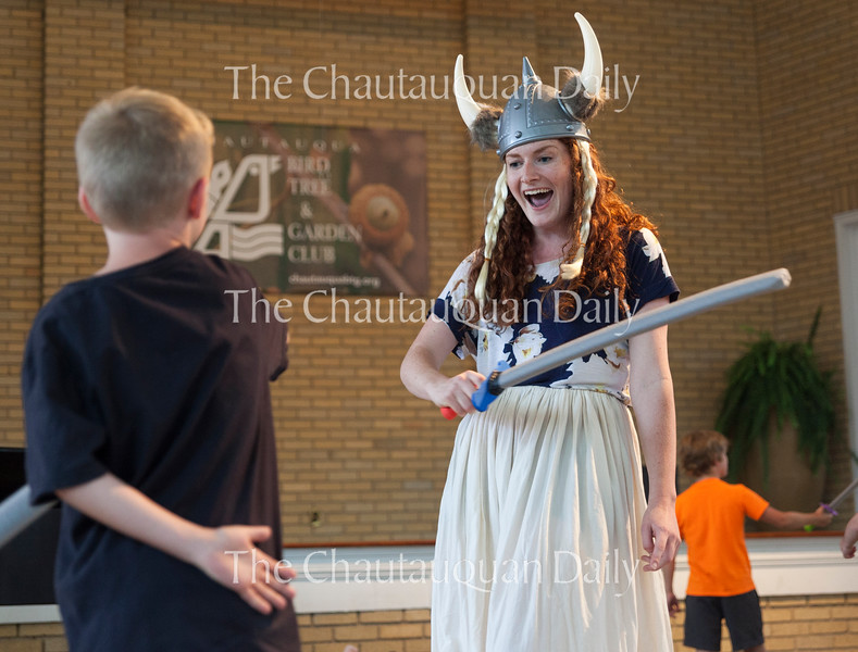 """Oliver Turfler, 8, left, swordfights with soprano Margaret Bridge, right, a Chautauqua Opera Young Artist, during """"Ride of the Valkyries"""" from Wagner's """"Die Walküre"""" at the Chautauqua Opera's event """"Hojo-To-Jo! To the Opera We Go!"""" at 5 PM on July 19, 2016, at Smith Wilkes Hall.<br /> <br /> At the event, Bridge and other members of the Chautauqua Opera Young Artist class of 2016 introduced children to opera by performing famous arias, teaching them opera vocabulary, and involving the audience in the show. Photo by Carolyn Brown."""