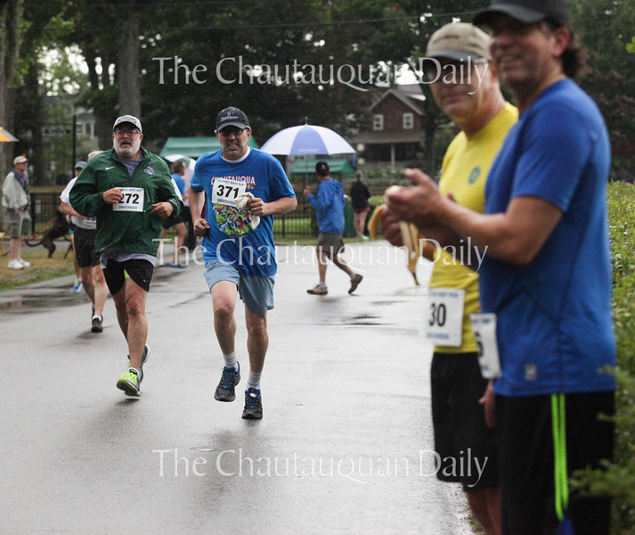 Allan Doctor, left, runs next to Guy Fustine, second from left, as Michael Metzger, second from right, and Rick Smith, right, watch the race at 8:30 A.M. on Saturday, July 30, 2016, outside the Sports Club. Competitor #287, 15-year-old Tyler Clark was the overall winner of the race. Photo by Carolyn Brown.