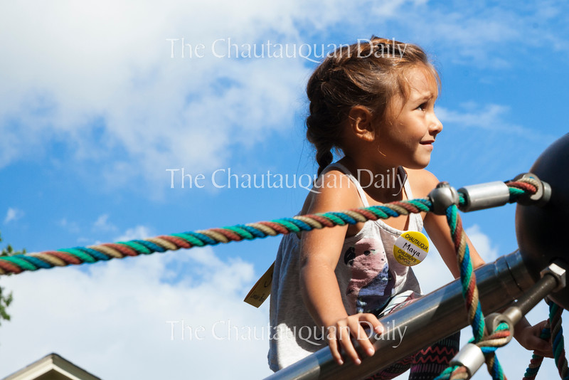 Maya Warren, five, plays on the climbing structure at 10 AM on July 15, 2016, at Children's School.<br /> <br /> Before participating in Children's School's Open House later that morning, the children and teachers in the Yellow Room, including Warren, did several activities, including playing with shaving cream, playing outside, and practicing the songs they would sing in the program. Photo by Carolyn Brown.