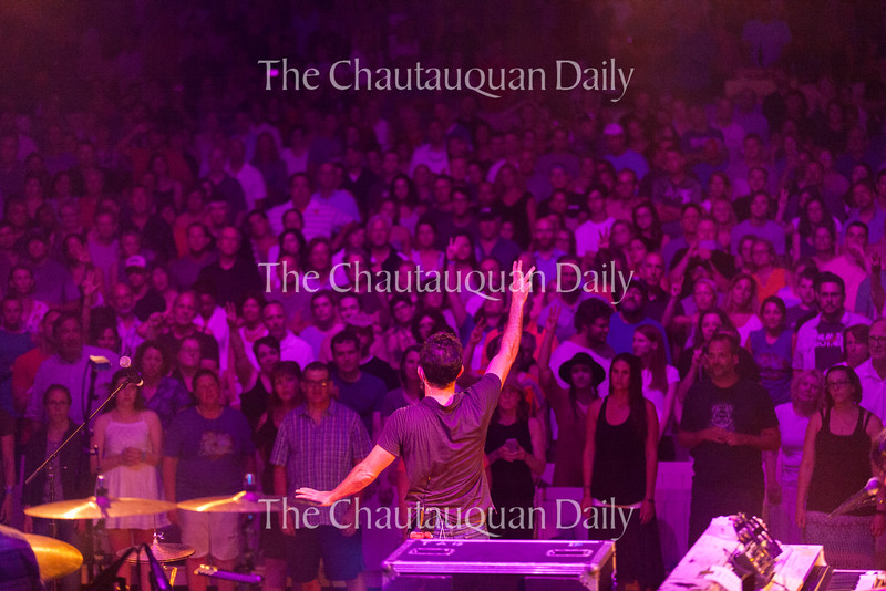 """Scott Avett of The Avett Brothers leads the audience in singing the refrain of the group's song """"I and Love and You"""" at 8:15 PM on July 8, 2016, at the Amphitheater. The show drew a sold-out crowd.<br /> <br /> Photo by Carolyn Brown."""