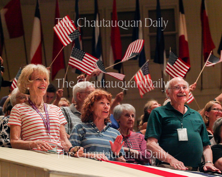 """Left to right: Susan Laubach, Lee Heinz, and Nelson Helm enjoy the music of """"The Stars and Stripes Forever"""" as people wave flags at the conclusion of the  Chautauqua Symphony Orchestra's Independence Day Pops Celebration concert at 10 PM on July 4, 2016, in the Amphitheater."""