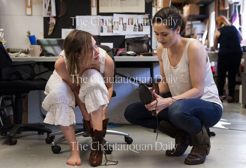 "Actress Allison Altman, left, talks to costume shop manager Janet O'Neill, right, as she puts on her character's costume shoes in Brawdy Theater Studios on June 27, 2016. Altman plays Sabrina Daldry in the Chautauqua Theater Company's production of ""In the Next Room (or the vibrator play.)""<br /> <br /> Photo by Carolyn Brown."