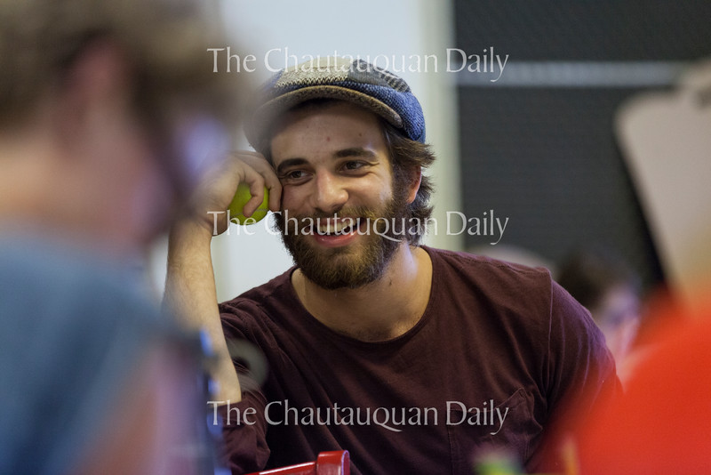 "Andrew Richardson laughs during a table reading of Chelsea Marcantel's ""Tiny Houses,"" one of the upcoming plays in the Chautauqua Theater Company's New Play Workshop, at 4:30 PM on July 11, 2016, in Studio B at Brawdy Theater Studios. Richardson plays the character Ollie, who sells haunted dolls on the Internet. Photo by Carolyn Brown."