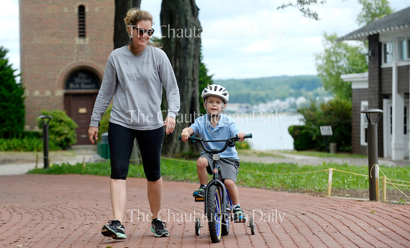 Mackenzie Oakley walks with her son Worth, 3, as he rides his bike in Miller Park Wednesday, June 29, 2016.