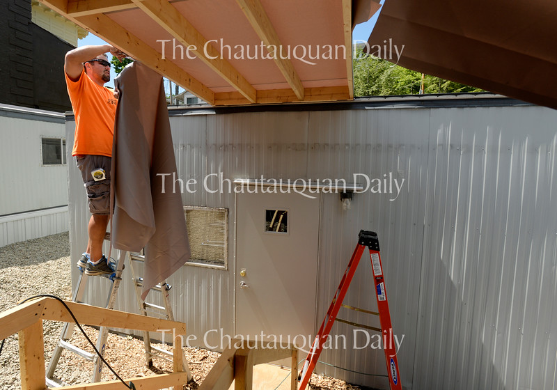 Scott Vincent, with Jamestown Awning, works in the Artist Village at the rear of the Amphitheater Tuesday, June 21.  Work is underway to prepare the Amp for the opening of the season on June 25.