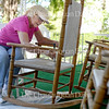 Karen Supparits gives a fresh coat of paint to porch chairs at the Carey Cottage Inn Friday, June 17, 2016.  Work is underway across the grounds to prepare for the opening of the season June 25.