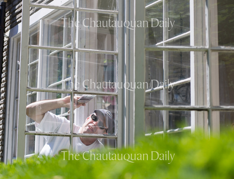 Larry Sweet paints the finishing touches on the windows of Diane R Bailey Antiques in the Chautauqua Institution on June 17, 2016. Many property owners on the grounds are preparing for the opening of the season on June 25.