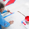 Dom Kimes, Artistic Director in the Visual Arts at Chautauqua Institution paints a mural on the crosswalk outside the Hultquist Center. Times hopes to finish the mural by Friday or Saturday in time for the seasons opening on June 25.