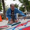 Don Kimes, the Visual Arts at Chautauqua Institution Artistic Director paints a crosswalk Monday, June 20, 2016, at Bestor Plaza. Kimes said the design he is painting is inspired by Pompeian mosaics.