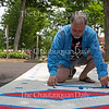 Don Kimes, the Visual Arts at Chautauqua Institution Artistic Director lays down tape while painting a crosswalk Monday, June 20, 2016, at Bestor Plaza. Kimes said the design he is painting is inspired by Pompeian mosaics.