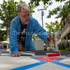 Don Kimes, the Visual Arts at Chautauqua Institution Artistic Director paints a crosswalk as Rev. Katie Eichenlaub White stops to chat Monday, June 20, 2016, at Bestor Plaza. Kimes said the design he is painting is inspired by Pompeian mosaics.