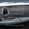 Jerry Coon pulls his kayak out of Chautauqua Lake before a storm on June 16, 2016.