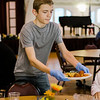 Fitchburg High student George Love serves guests during a pasta dinner put on by the Fitchburg Holiday Decorating Committee on Wednesday evening at the Fitchburg Senior Center. Food donations were given by Pastaland, Midtown Beef and Cormier Catering. SENTINEL & ENTERPRISE / Ashley Green
