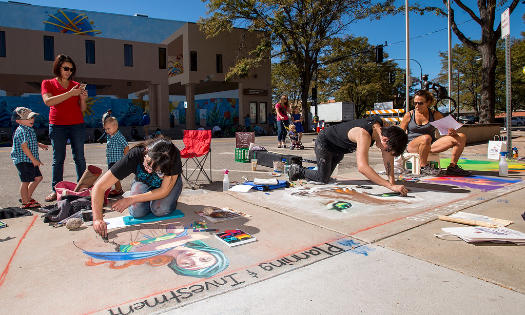 . Jackie Burrington, and her sons Cayson, 4, left, and Quinn, 2, right, from Berthoud, watch artists, left to right, Amanda Gress, Dakota Sena, and Cynthia Danielle Saturday morning Sept. 10, 2016 during the Pastels On 5th sidewalk chalk festival in downtown Loveland. The free event highlights the thriving Loveland arts community and attracts artists and attendees from all over northern Colorado. (Photo by Michael Brian/Loveland Reporter-Herald)