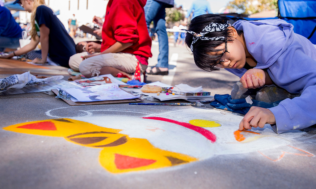 . Artist Lili Gurski, from Fort Collins, works intently on her Pastels On 5th sidewalk chalk art festival entry Saturday morning Sept. 10, 2016 along East Fifth Street in Loveland. (Photo by Michael Brian/Loveland Reporter-Herald)