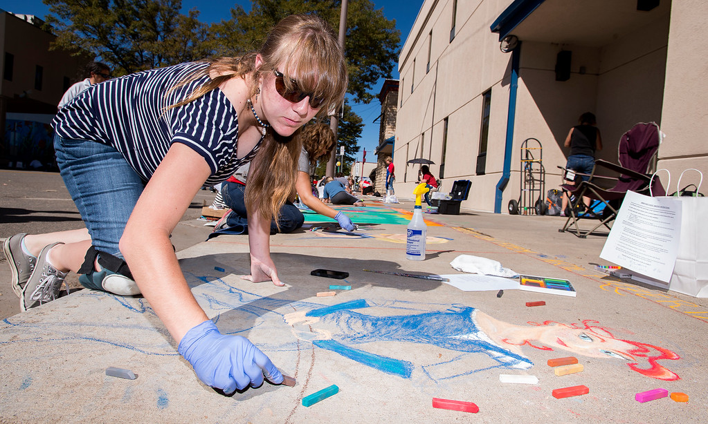 . Artist Tori Puckosh, from Fort Collins, works on her Pastels On 5th sidewalk chalk art festival piece Saturday morning Sept. 10, 2016 in front of the Reporter-Herald building on East Fifth Street in Loveland. The event is designed as a benefit for Alternatives to Violence, an organization committed to the intervention in, education about, and prevention of domestic violence, sexual assault, and other violent crimes. (Photo by Michael Brian/Loveland Reporter-Herald)